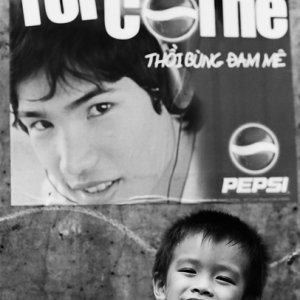 Boy ginning in front of advertisement