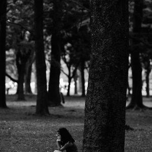 木立の中にしゃがむ女の子