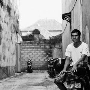バイクの上に腰掛けいた若い男