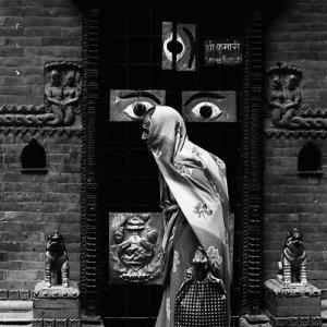 瞳が描かれた扉の前を歩く老婆