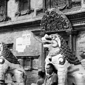 Man leaning against statue of lion