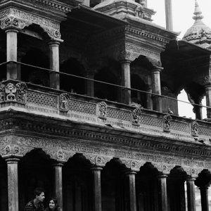 Couple enjoying chatting under eaves of Hindu temple