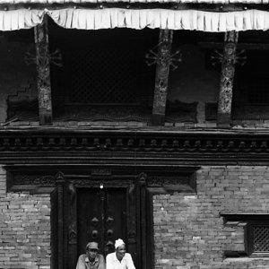 Men sitting together in front of wooden door