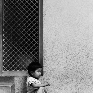 Little kid sitting alone under eaves
