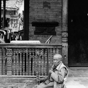 Old monk holding prayer wheel