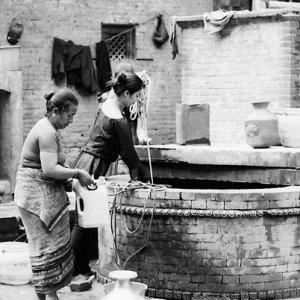 井戸で水汲みをする女たち