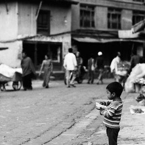 Shoeless boy standing alone by roadside