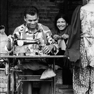 足踏み式のミシンで仕事する男