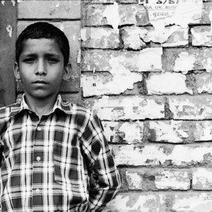 煉瓦造りの壁に寄りかかる男の子