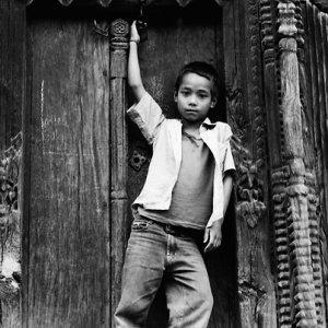 木製の扉の前でポーズを決める男の子