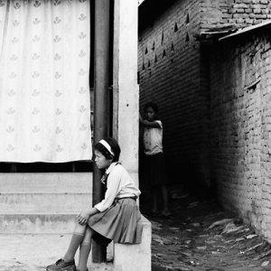 道端に腰掛ける女子学生