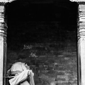 Man sleeping between wooden pillars