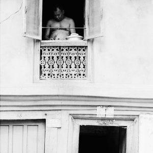 Man cooking by upstairs window