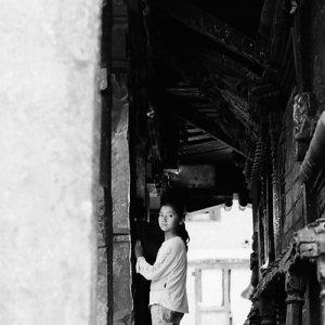 Girl looking back in corridor of temple