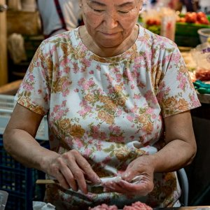 Woman wrapping minced flesh