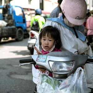 Girl on motorbike with mother
