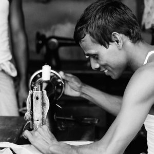 Man manipulating sewing machine