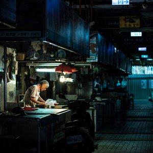 man working in dim Shuixian Temple Market