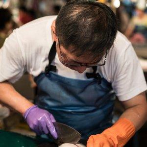 Fishmonger cutting a fish