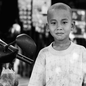 Boy standing beside motorbike