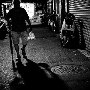 傘とビニール袋を持って歩くシルエット