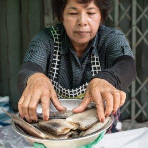 計量器で魚を量る女