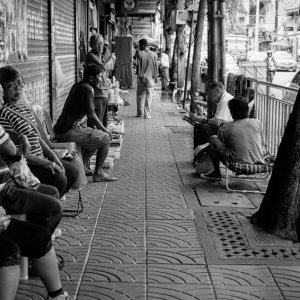 People relaxing on sidewalk