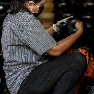 托鉢用の鉢を塗る女
