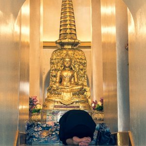 Woman bowing down on knees in Wat Saket