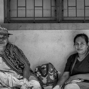 Women sitting against wall