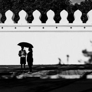 ひとつの日傘の下に立つふたりのシルエット