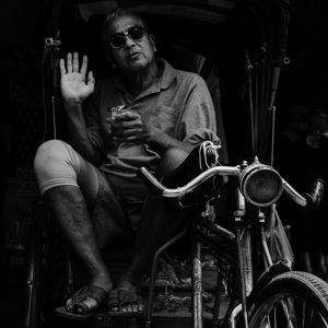 自転車タクシーに乗っていたサングラスを掛けた男