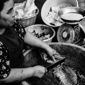バケツの中に置いた俎板の上で魚を捌いていた女