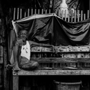 Old man sitting on wooden bench