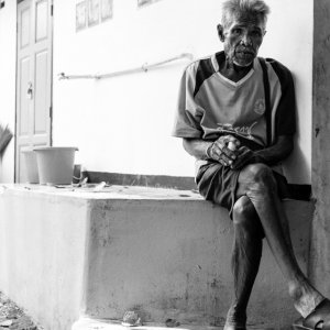 路地の片隅に腰掛けていた老人