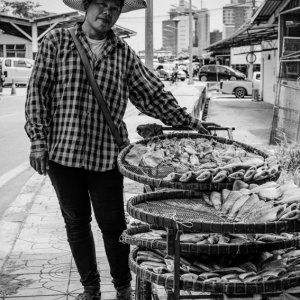 Woman selling dried fishes on sidewalk