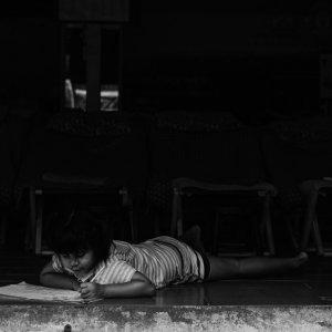 Girl studying while lying flat