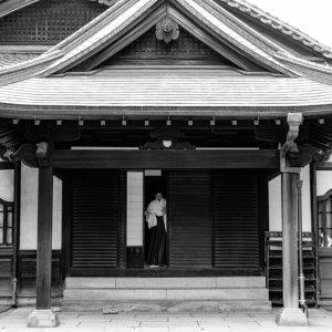 Shinto priestess getting into a building