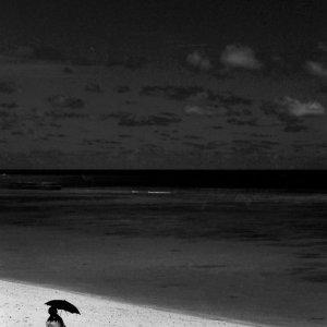 ニシ浜を歩く黒い日傘を差した女性