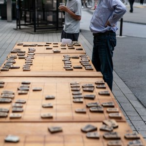 Man watching another man playing Shogi