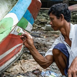 Man recoloring fishing boat