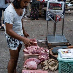 肉の塊を売る男