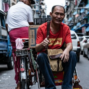 Man thumbing up on seat of pedicab