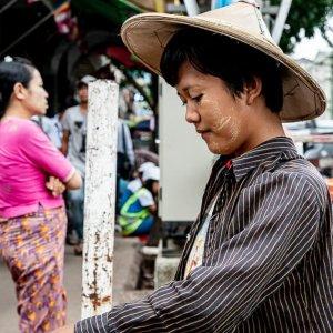 露天市でオレンジを売る若い女性