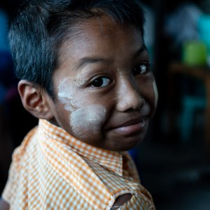 Boy with Thanaka on his face looking back