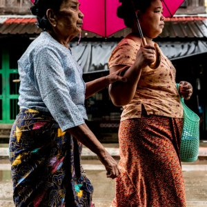 Two women walking together in drizzle