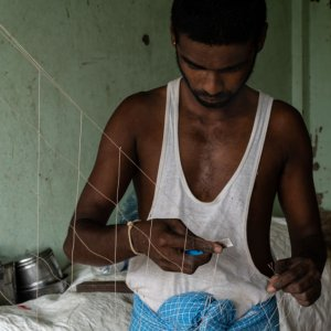 Man repairing fishnet with razor