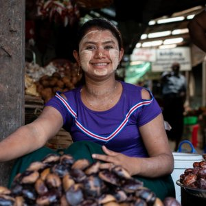 Smiling woman selling chestnuts
