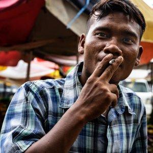 煙草を吸いながら見つめる男