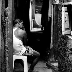 薄暗い路地で休む男